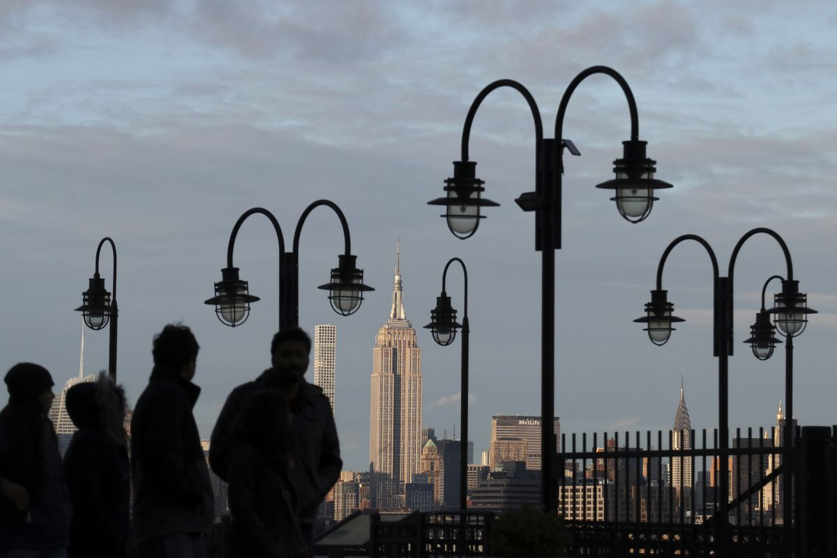 People walk along a parkway with overhanging lamps with the NYC skyline in the background