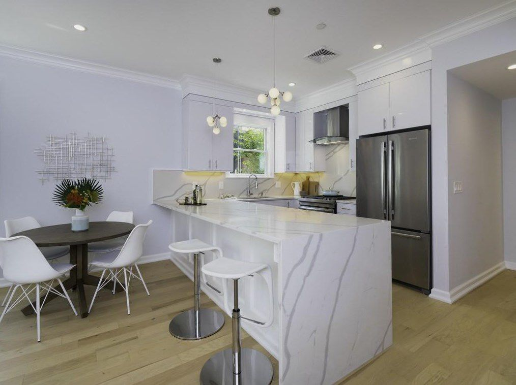 An eat-in kitchen featuring a large granite island with stools in front of it.