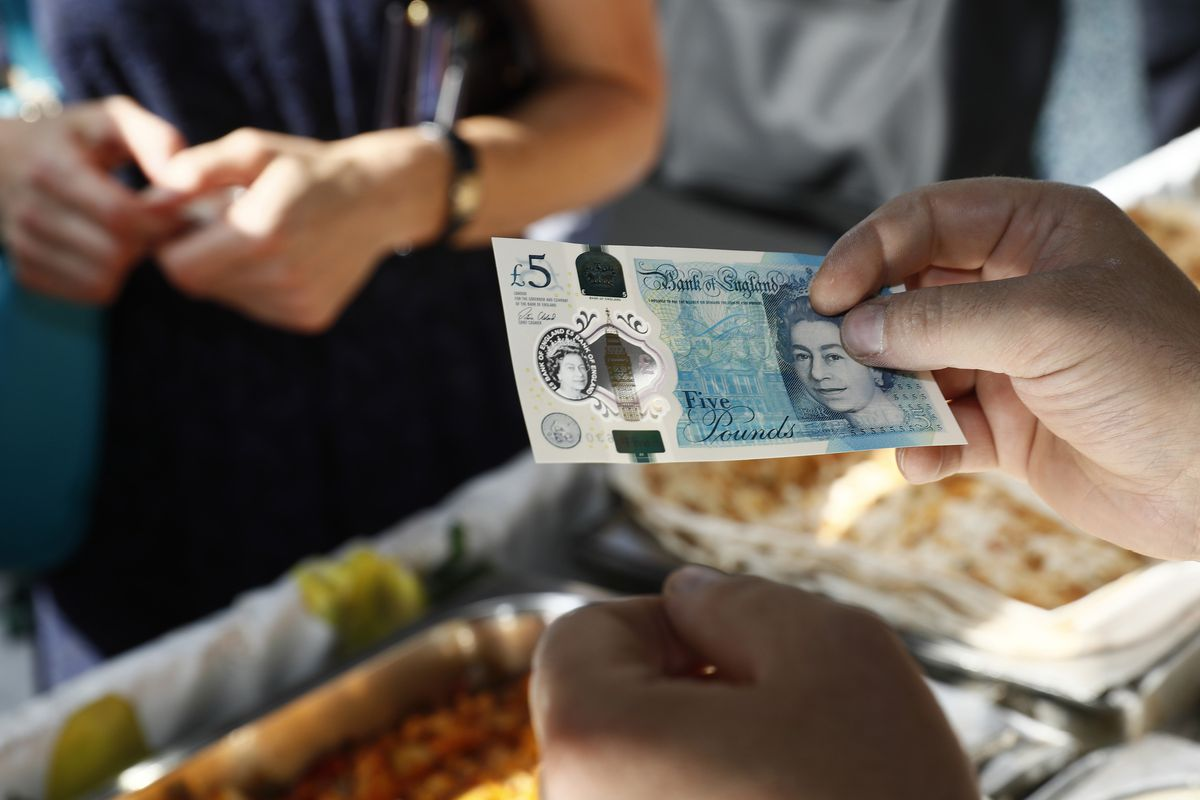 A shopper makes a purchase by handing over a five pound note.