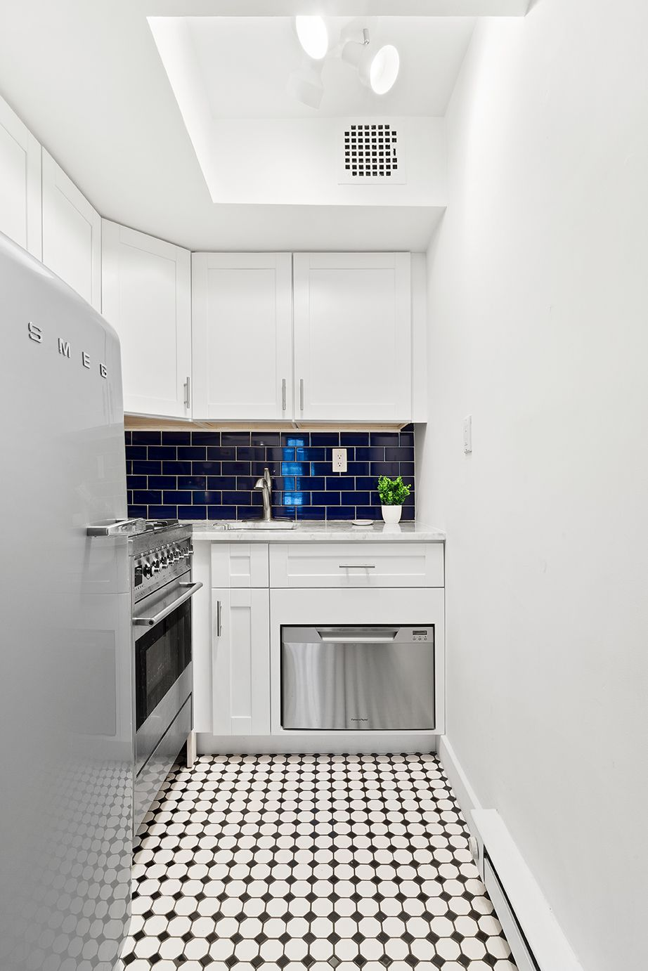 A kitchen with black and white tile floor and white cabinetry.