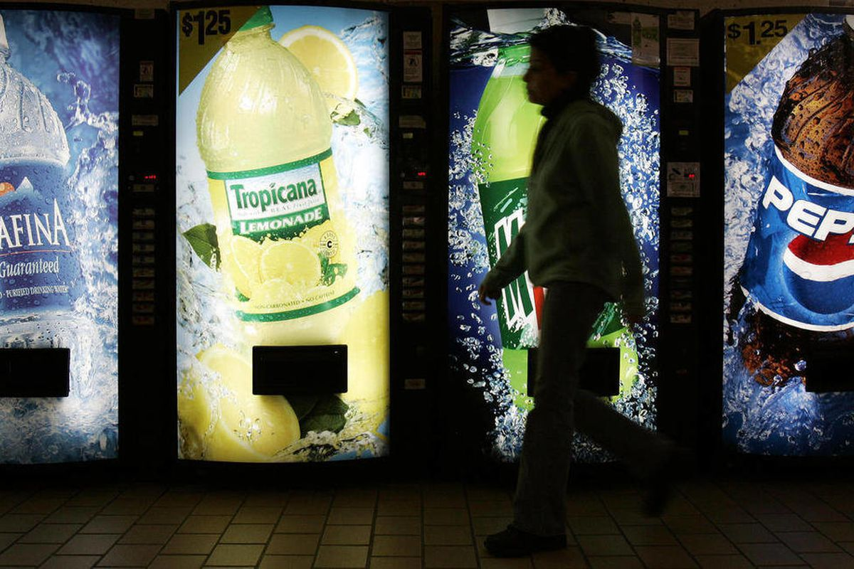 FILE - In this Feb. 7, 2006, file photo, a student walks past PepsiCo vending machines in Cleveland. PepsiCo Inc. reported Thursday, April 26, 2012, that its first-quarter net income fell slightly from a year ago, earning $1.13 billion, or 71 cents per sh
