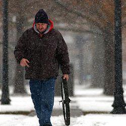 Aleks Golub carries a bicycle wheel as he trudges through Pioneer Park in downtown Salt Lake.