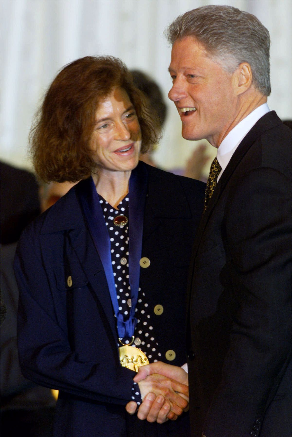 Martha Lavey, artistic director of Steppenwolf Theatre, wears the 1998 National Medal of Arts Award presented to the theater by President Clinton during a ceremony at the White House. | AP Photo/Doug Mills