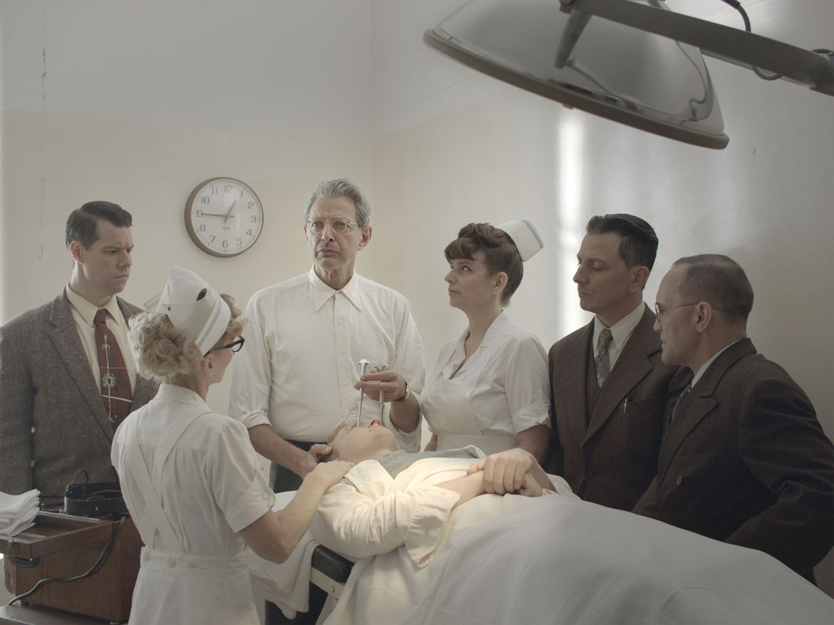 Surrounded by hospital staff, Fiennes (Jeff Goldblum) poses with an icepick held above a patient's eye.
