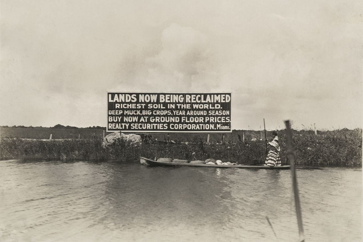 A Seminole woman poling past a billboard advertising the sale of reclaimed land in the Everglades, circa 1920.