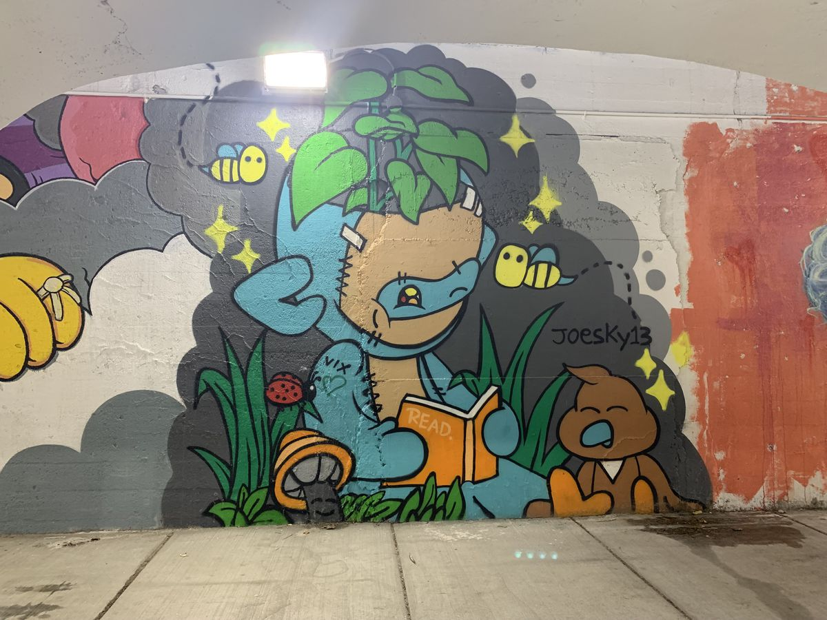 """This mural by Edgewater artist Joesky includes a character that's """"supposed to be a futuristic Teddy bear"""" encouraging """"kids to read more."""" He says that, with the pandemic, """"They're just stuck in technology a lot and stuck at home,"""" and he wants them to """"learn more things, not just video games."""""""