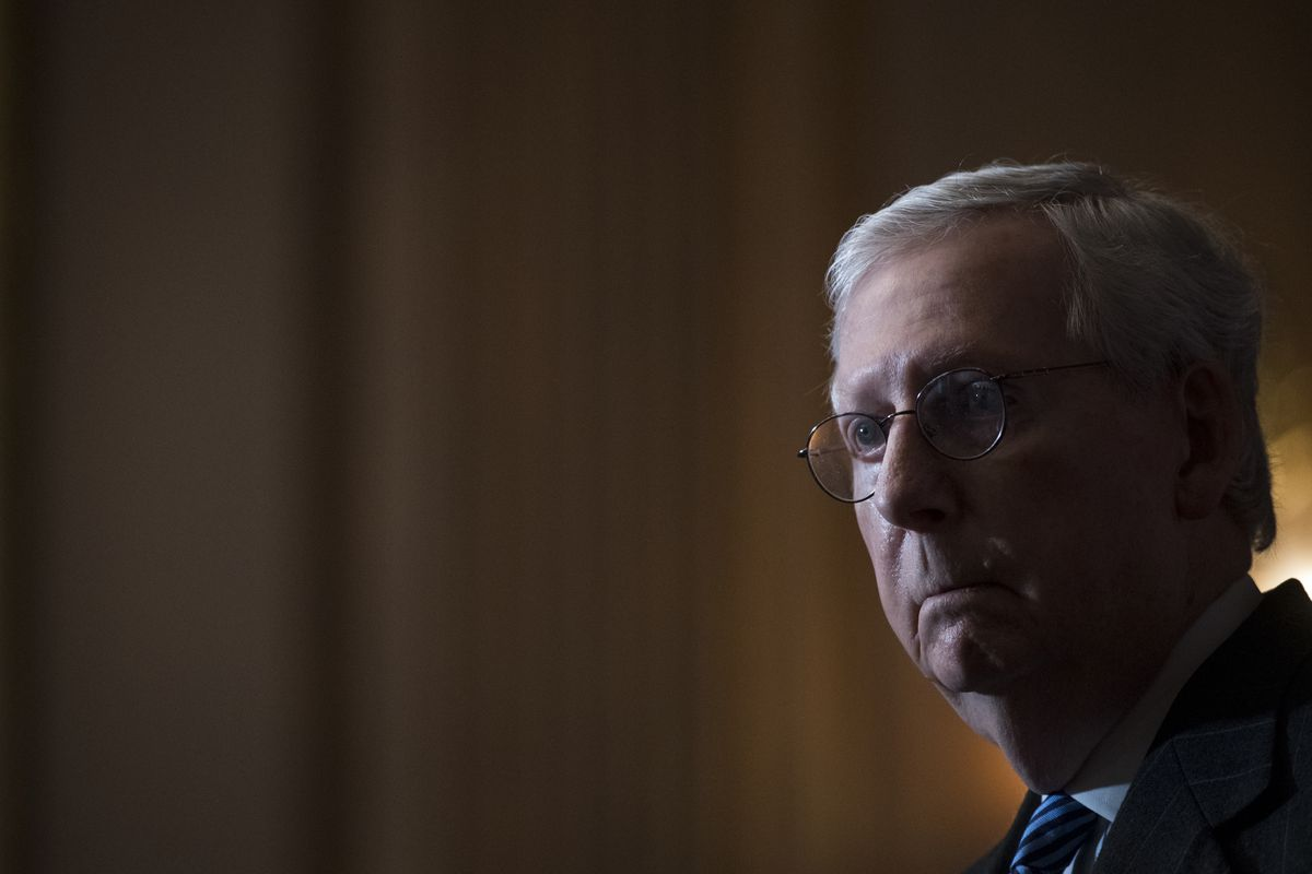 A backlit Mitch McConnell ominously addresses reporters.