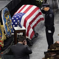 An officer salutes the casket of Unified police officer Doug Barney during funeral services at the Maverik Center in West Valley City on Monday, Jan. 25, 2016.