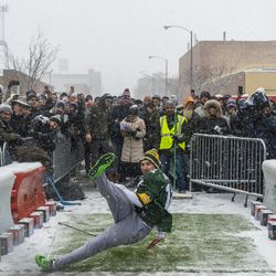 A man falls after attempting to kick a football 43 yards to win NFL tickets to any game, outside Goose Islands Tap House, Saturday, Jan. 12, 2019, in Chicago. Goose Island sponsored the event encouraging participants to attempt a similar field goal that Chicago Bears Kicker Corey Parkey missed in a playoff game against the Philadelphia Eagles which resulted in the Bears losing the game.   Tyler LaRiviere/Sun-Times