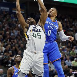 Utah Jazz guard Donovan Mitchell is defended by Oklahoma City Thunder guard Russell Westbrook during NBA basketball in Salt Lake City on Saturday, Dec. 23, 2017.