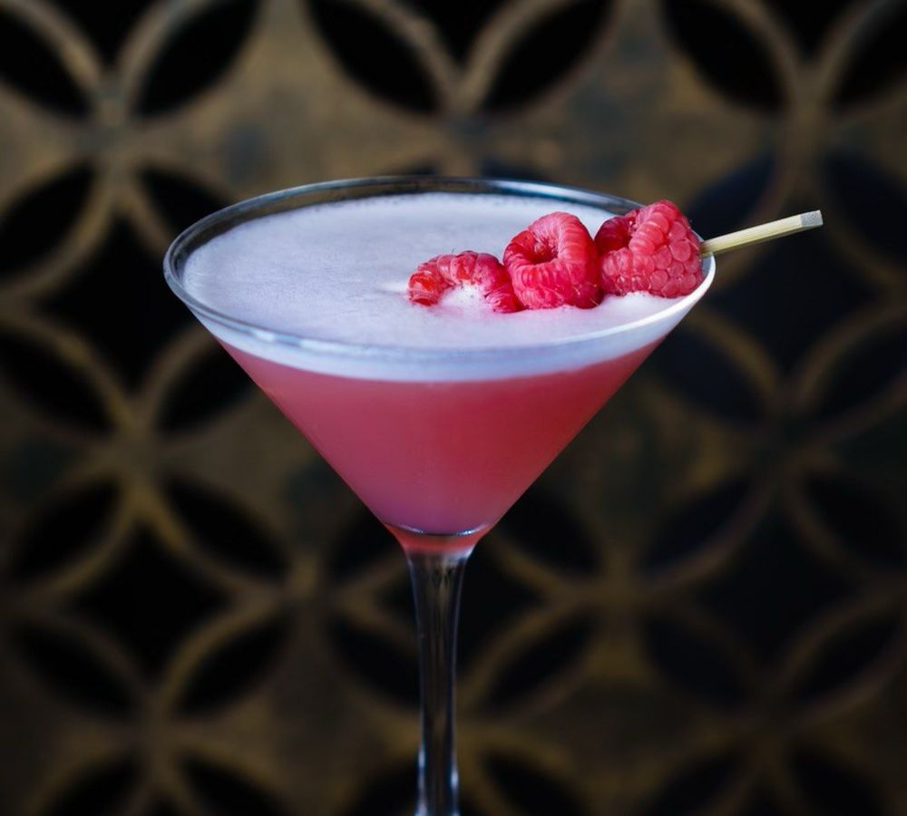 The Tao Tini at Tao Chicago. The pink drink sits in a martini glass, topped with a skewer of raspberries.