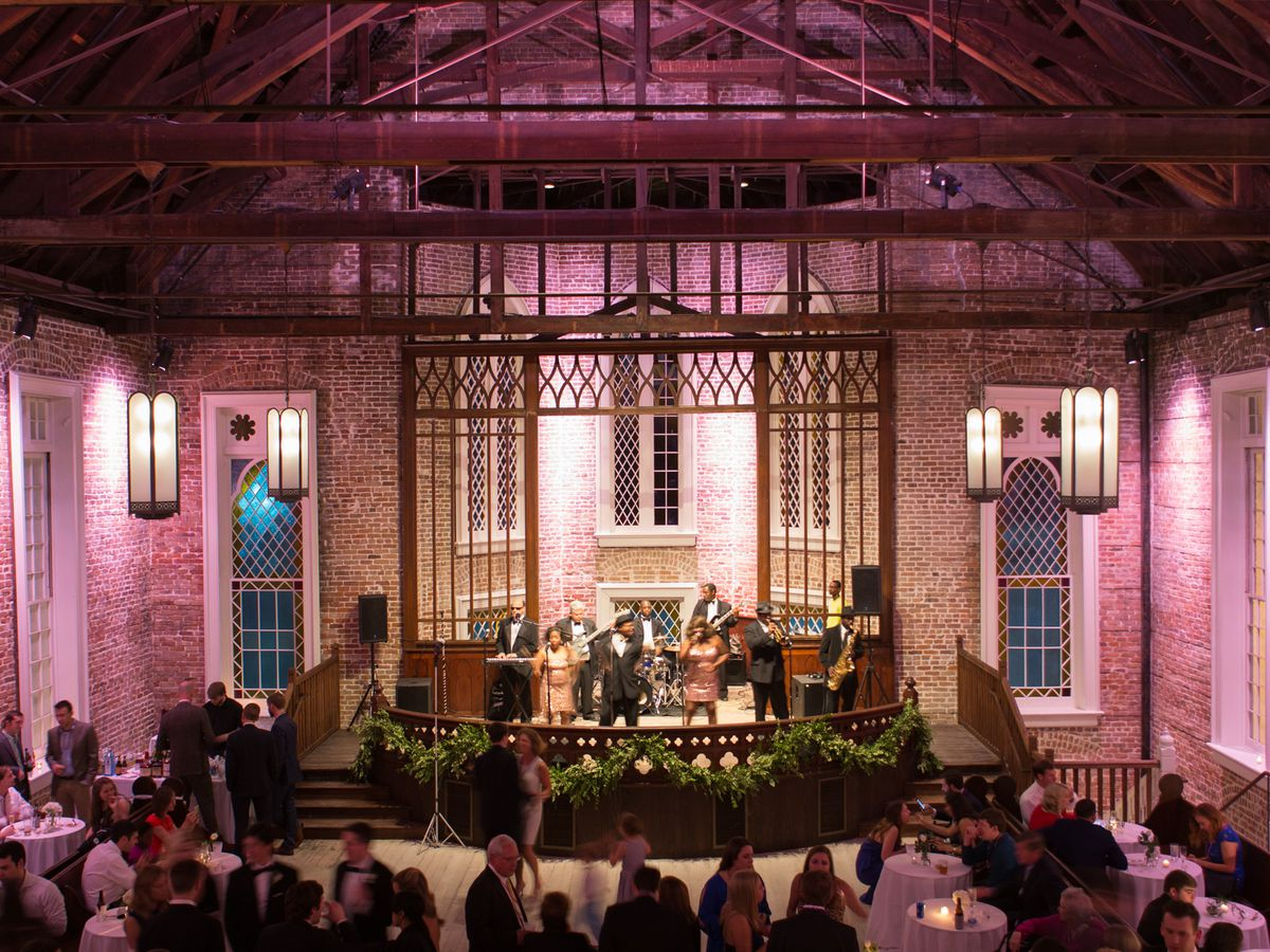 The interior of the Felicity Church in New Orleans. The walls are exposed brick and there are pink lights illuminating the interior. There are rows of benches and an altar.