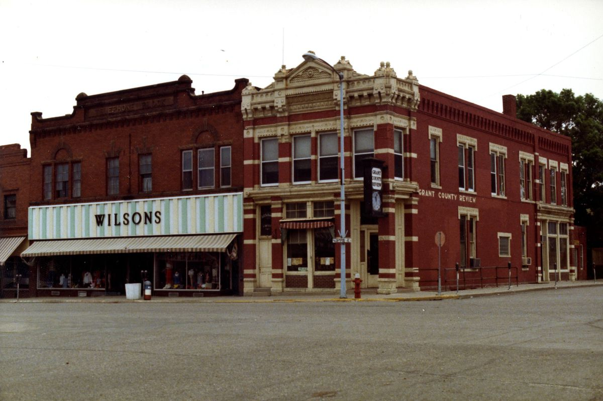 A 1978 photo of a department store and a corner brick building in Milbank, South Dakota.