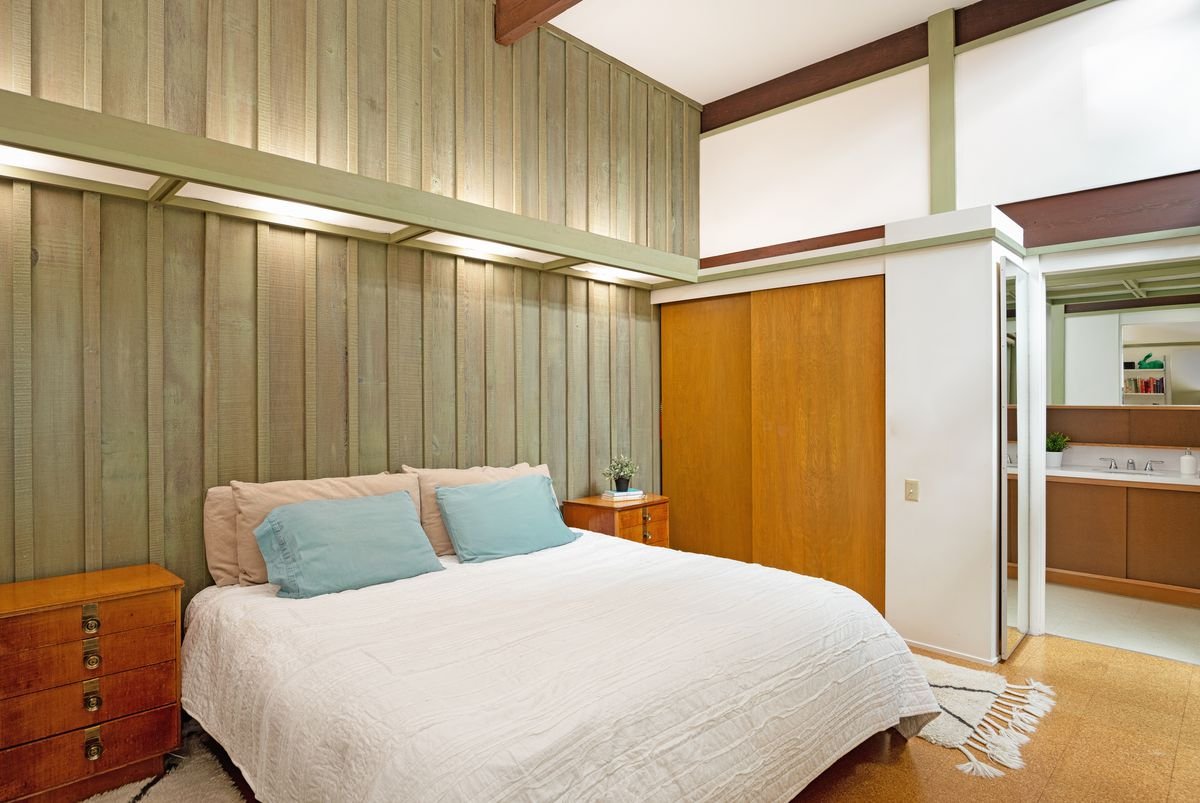 A room with pale green wooden walls, furnished with a large bed and a small dresser