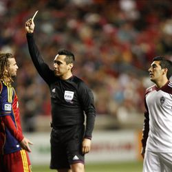 Kyle Beckerman of Real Salt Lake gets a yellow card from referee Jair Marrufo and in front of Martin Rivero of the Colorado Rapids during their MLS match up at Rio Tinto Stadium in Sandy Saturday, April 7, 2012.