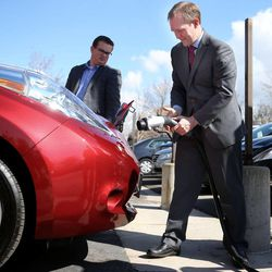 Salt Lake County Mayor Ben McAdams plugs a Nissan Leaf into a newly-installed electric vehicle charging infrastructure at the Salt Lake County building in Salt Lake City on Thursday, April 3, 2014. Justin Miller, left, associate deputy mayor, looks on.