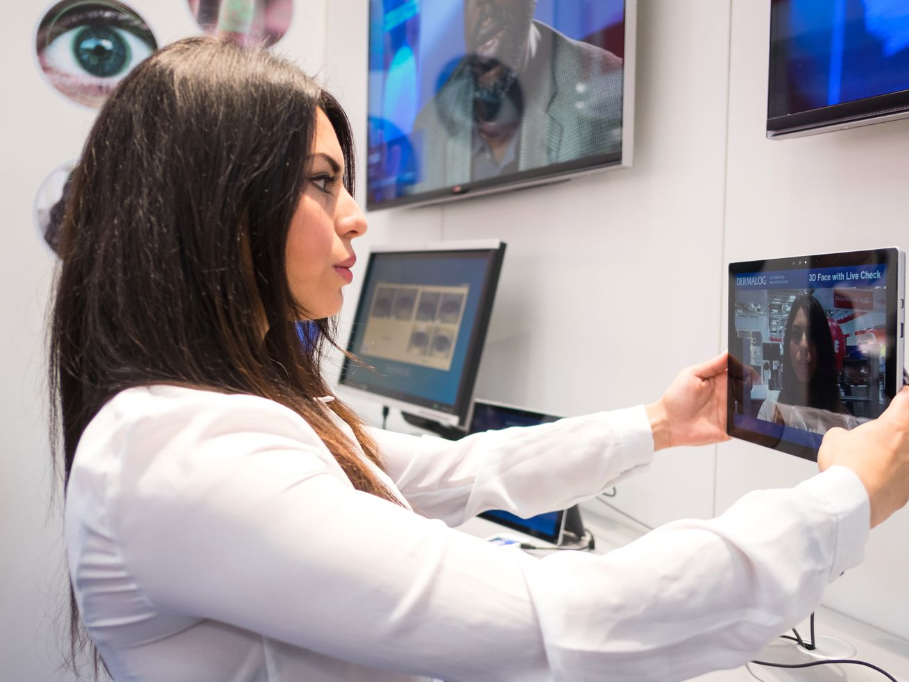A woman holds a tablet featuring biometric 3D facial recognition software.