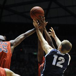 Utah Utes guard Delon Wright (55) fights for a rebound with a teammate and Brigham Young Cougars forward Josh Sharp (12) during a game at the Jon M. Huntsman Center on Saturday, Dec. 14, 2013.