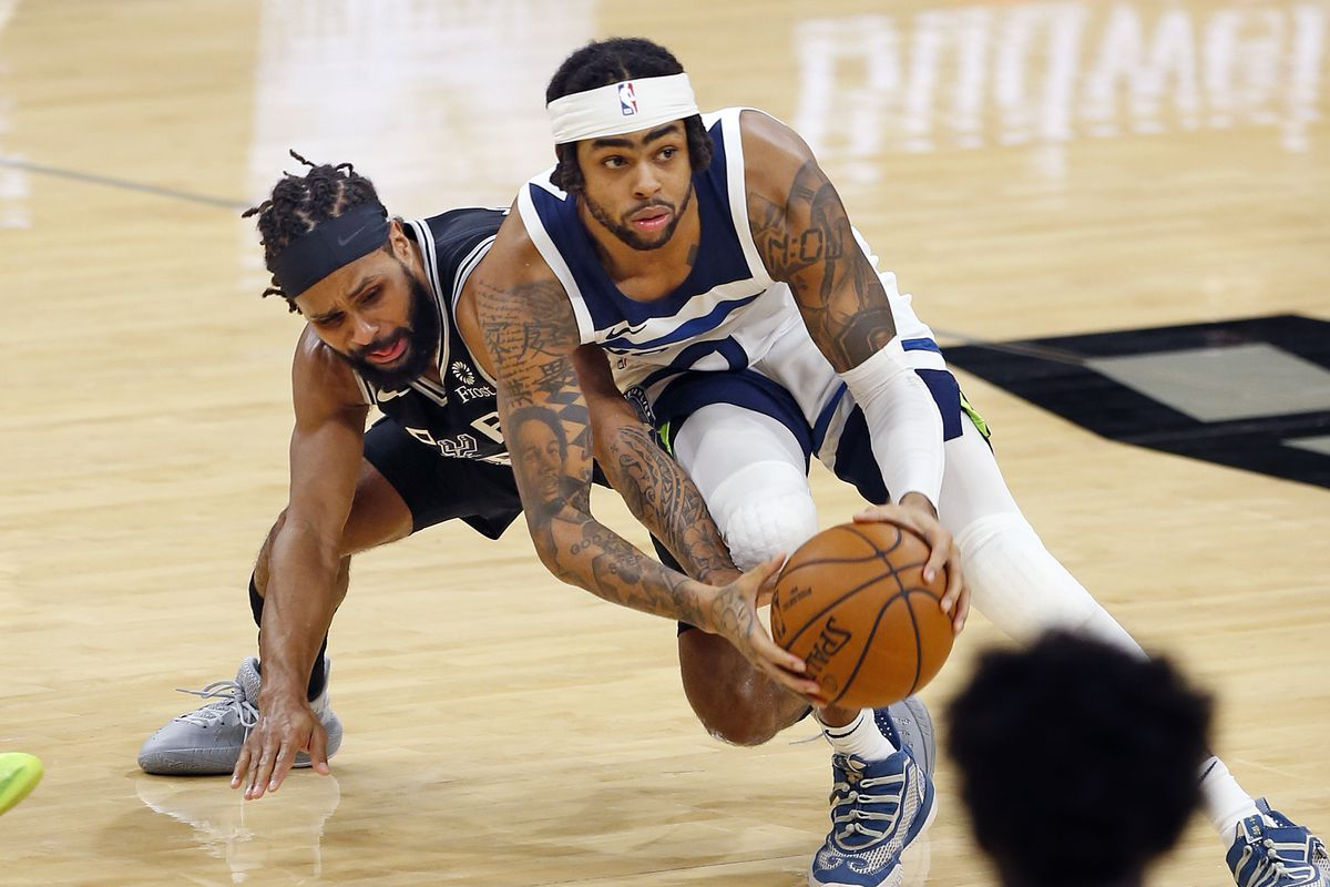 Patty Mills of the San Antonio Spurs tries to steal the ball from D'Angelo Russell of the Minnesota Timberwolves during the second half at AT&T Center on February 3, 2021 in San Antonio, Texas.