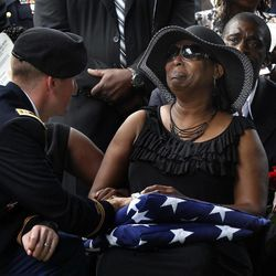 FILE - In this Wednesday Aug. 1, 2012 file photo, Casualty Affairs officer Capt. Miles Wilhelm comforts Tracy M. Hicks during the interment of her son Cpl. Darrion Terrell Hicks at Raleigh National Cemetery in Raleigh, N.C. Hicks died from injuries sustained from an improvised explosive device in Ghazni, Afghanistan, July 19, 2012. Eleven years after the U.S. began battling to rid Afghanistan of al-Qaida and the Taliban, the war has ebbed from the headlines. The question of just how to end it is barely mentioned in the speeches of this year's presidential campaign. Polls find most Americans just want it over.