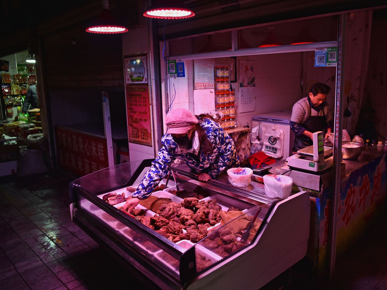 Vendors, wearing face masks, selling meat in a dimly lit market.
