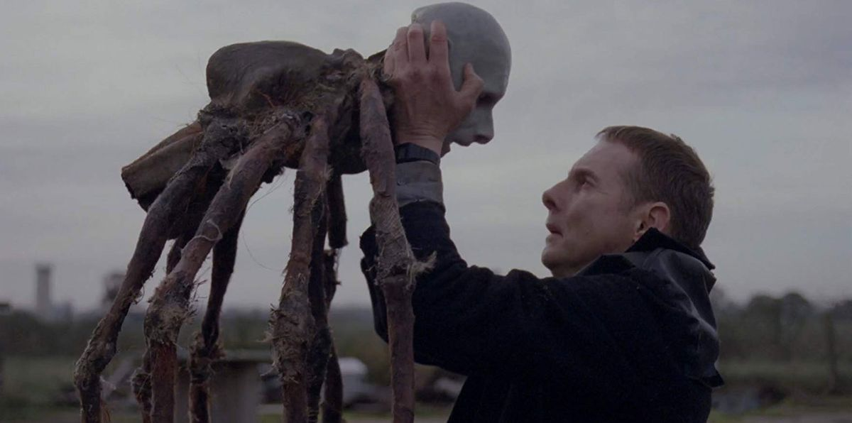 a man holds a spider creature with a decaying human head