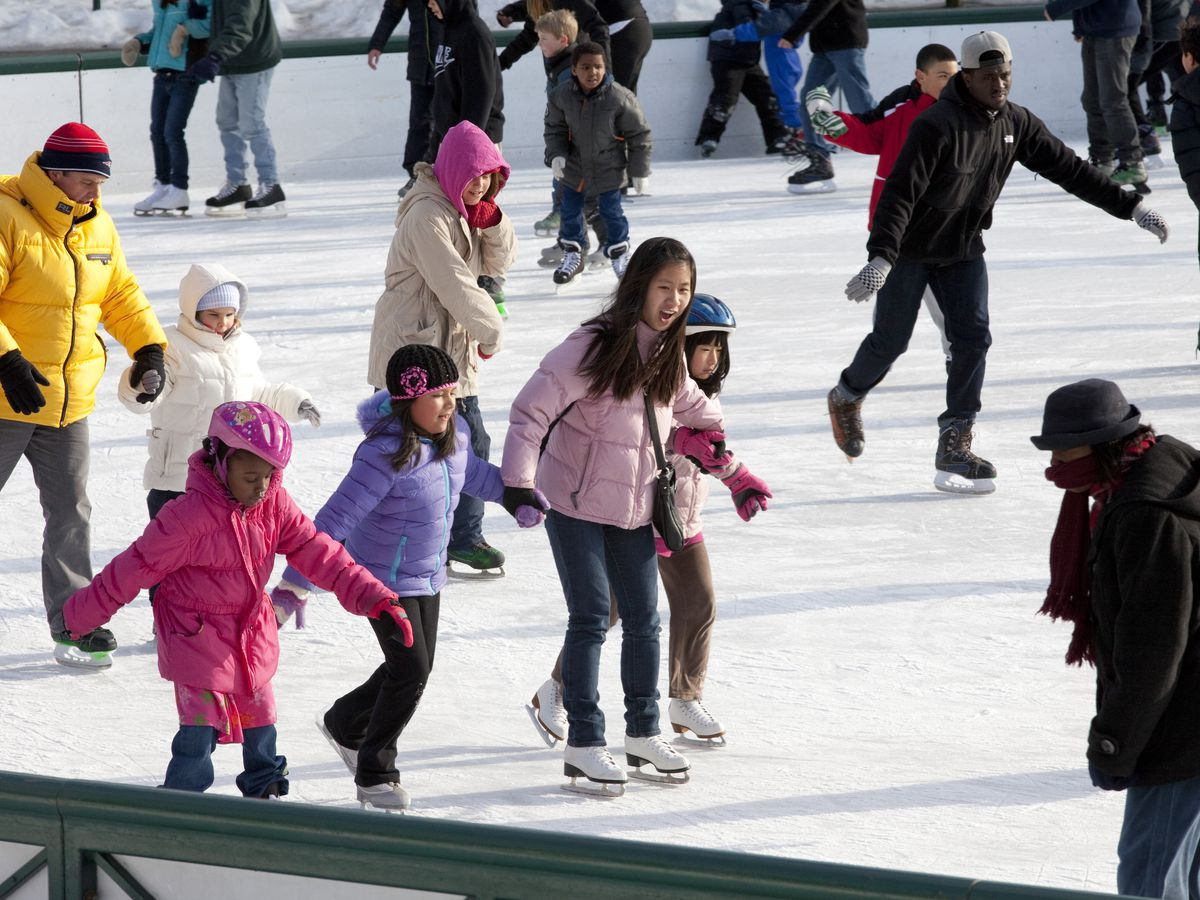 People joining hands and ice-skating on an outside rink.