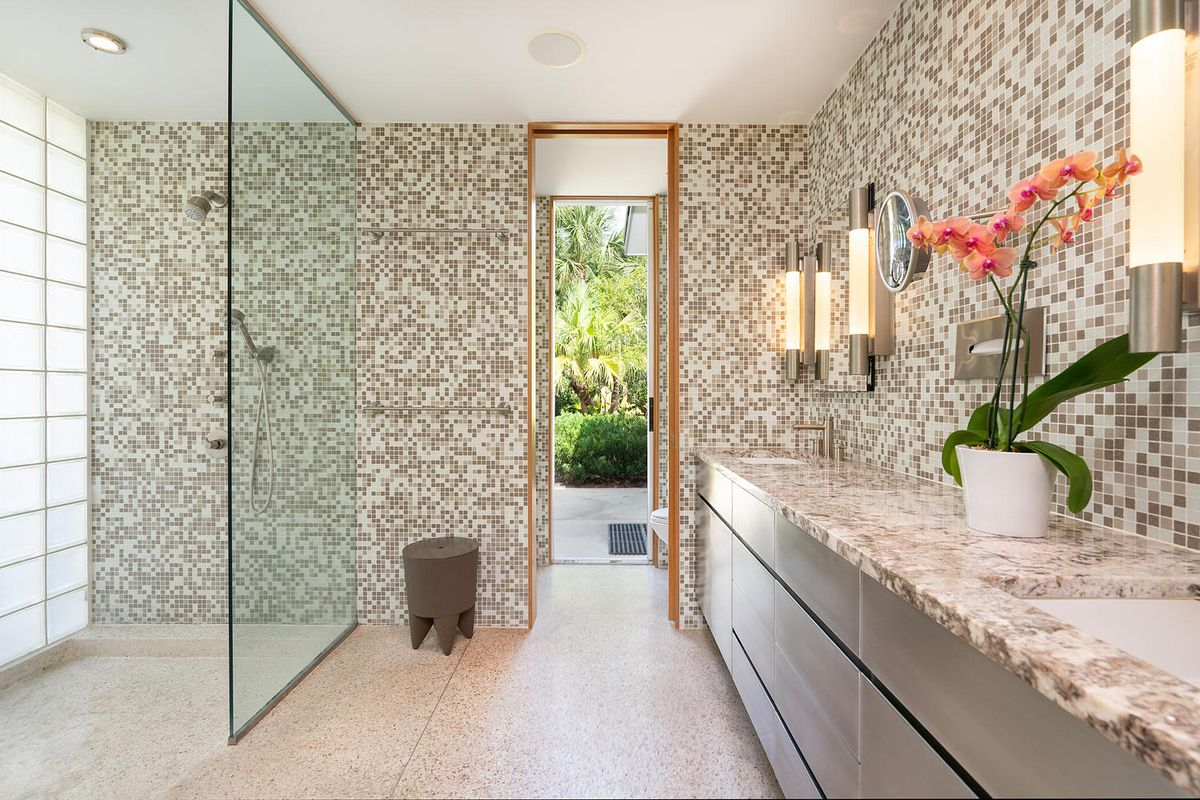 A tiled bathroom has marble counters, brown cabinets, and an open shower.