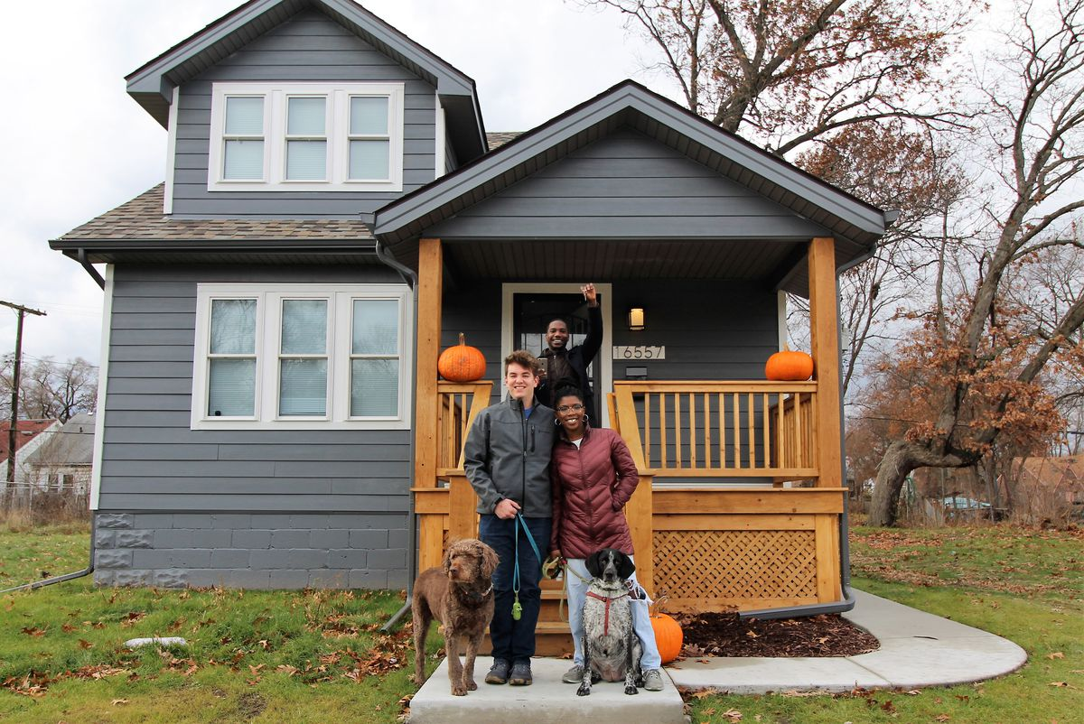A couple stands in the front walkway of a gray home, smiling. They hold two dogs on leashes. Another man stands behind them on the porch, also smiling, with his fist in the air.