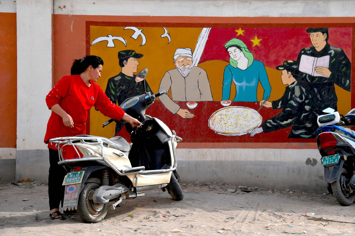 A Uighur woman beside a propaganda painting showing soldiers meeting with a Uighur family, in China's northwest Xinjiang region.