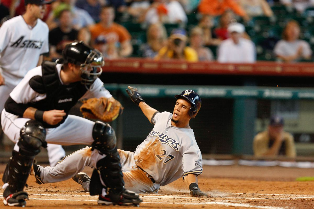 Aug 12, 2012; Houston, TX; USA; Milwaukee Brewers center fielder Carlos Gomez (27) beats the throw to Houston Astros catcher Chris Snyder (18) to score a run during the second inning at Minute Maid Park. Mandatory Credit: Thomas Campbell-US PRESSWIRE