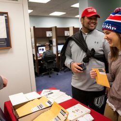 Uliti and Kelsey Fangupo, of Orem, pick up their inauguration ceremony tickets from Rachel Evans, left, assistant to the chief of staff to Sen. Orrin Hatch, R-Utah, in Hatch's office at the Hart Senate Office Building in Washington, D.C., on Thursday, Jan. 19, 2017.