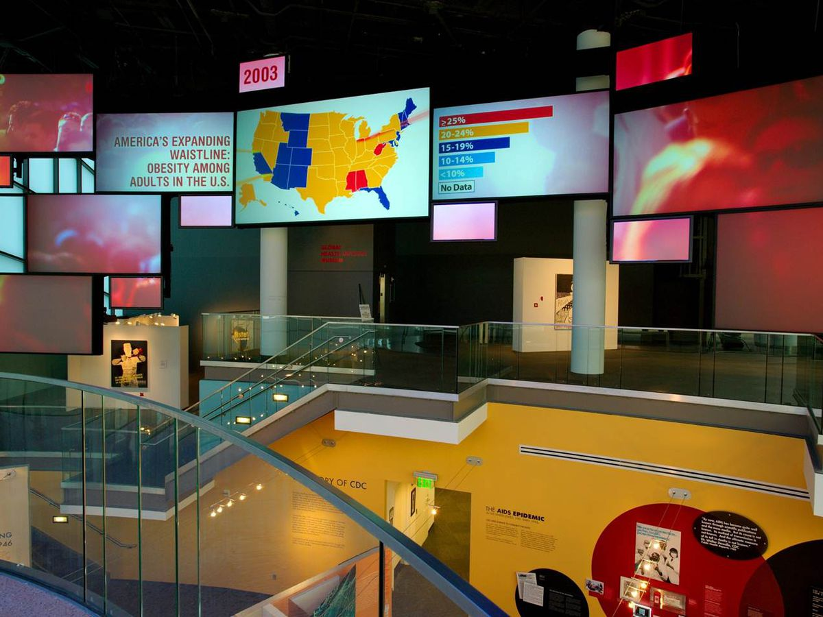 A wall outfitted with TV screens and bright colors documenting public health history.