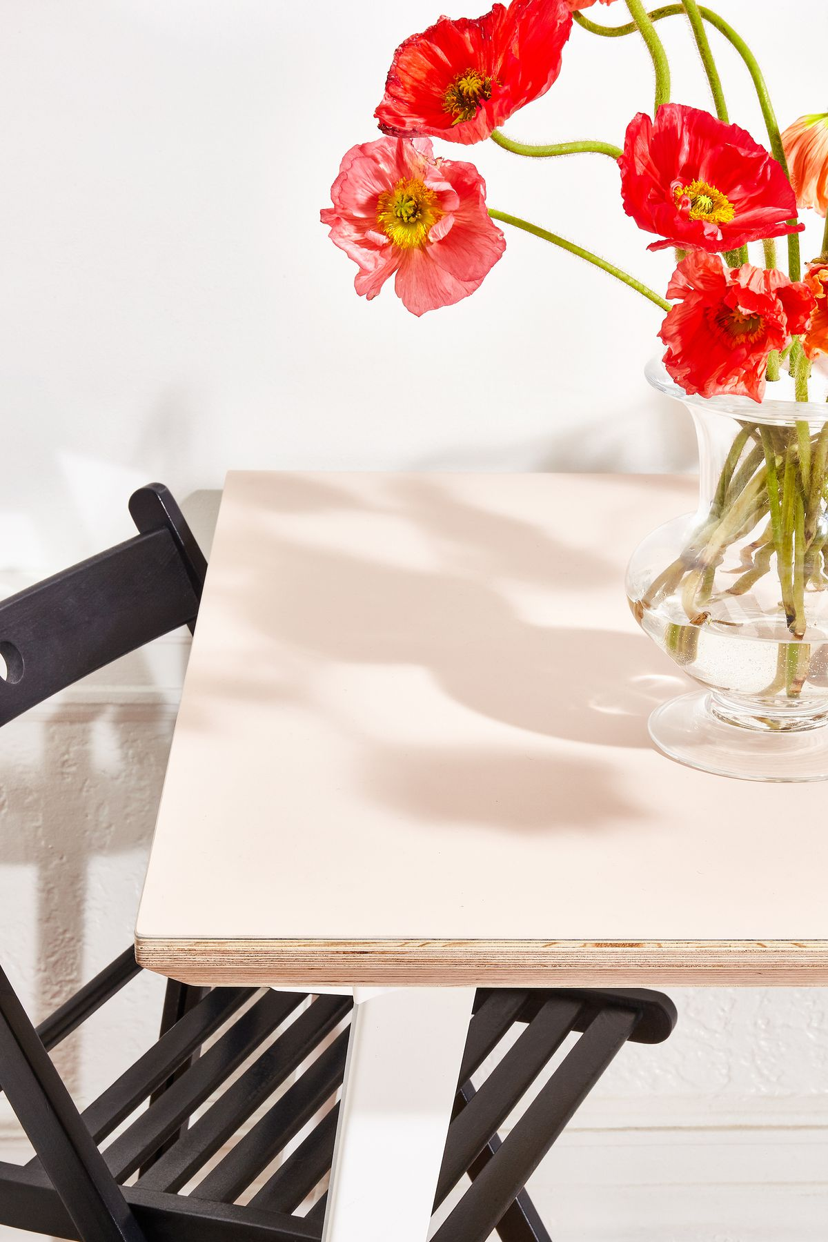 A pale pink table with white legs, a black folding chair, and red poppies in a clear glass vase.
