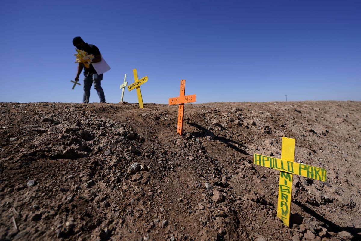 Hugo Castro leaves crosses at the scene of a deadly crash in Holtville, Calif., Tuesday, March 2, 2021. Authorities say a semitruck crashed into an SUV, killing multiple people.