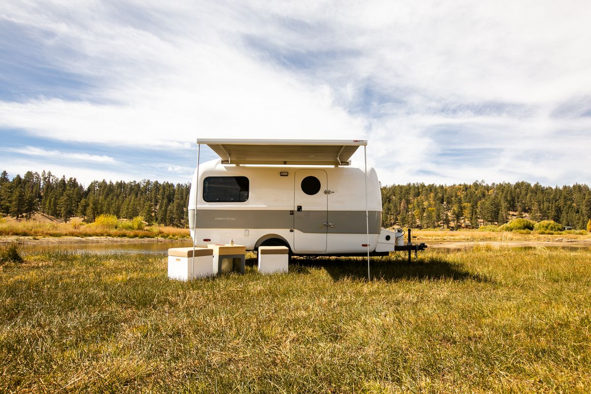A two-toned white and light green travel trailer sits in a field with its awning out.