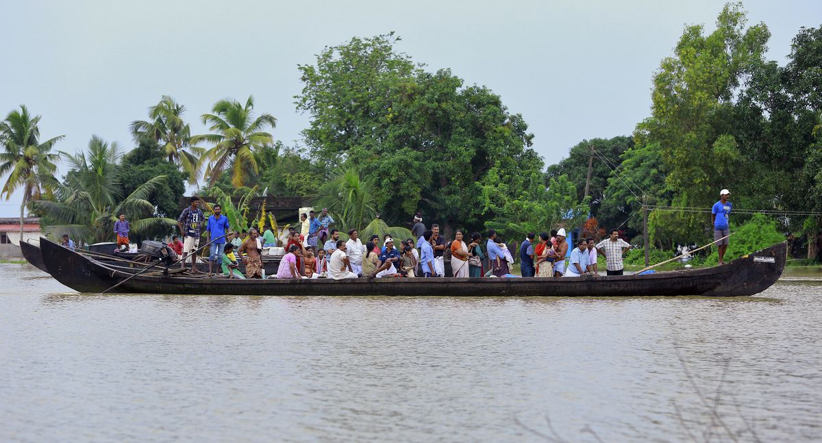 People wait to be rescued in a country boat in a flooded area at Kainakary in Alappuzha district, Kerala state, India, on August 17, 2018.