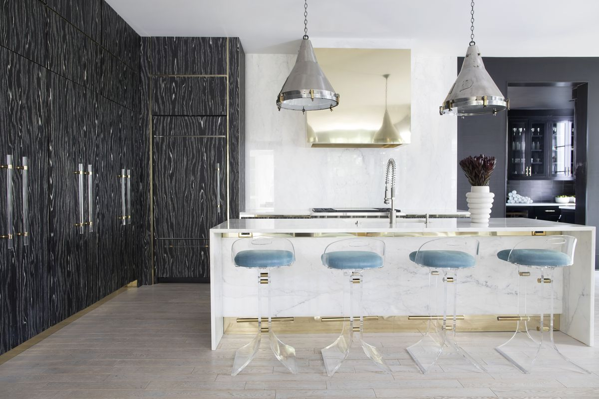 A brass range hood makes a statement in a white kitchen with black cabinets.