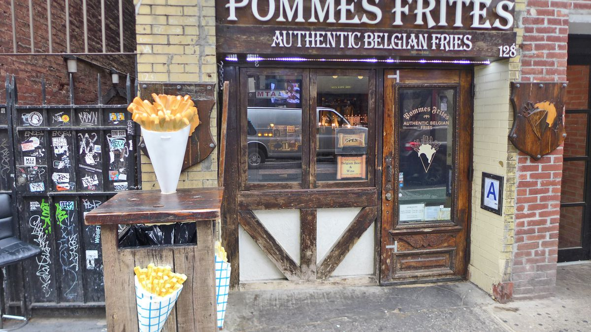 The front of the store has timbers implanted in the stucco facade, with several models of french fries in papers cones on display.