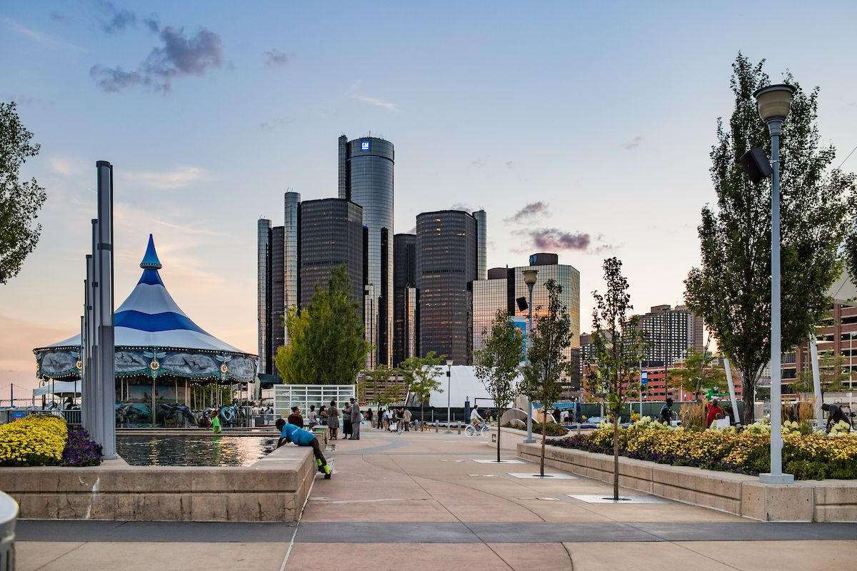 In the foreground is a pedestrian plaza with people. In the distance is a city skyline with tall buildings.