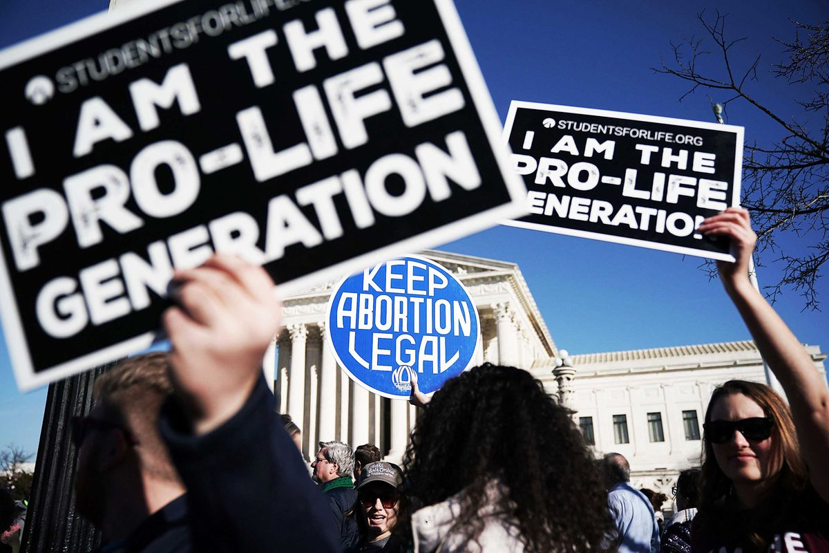 """Activists hold up competing signs at a protest in front of the Supreme Court: """"I am the pro-life generation"""" and """"Keep abortion legal."""""""