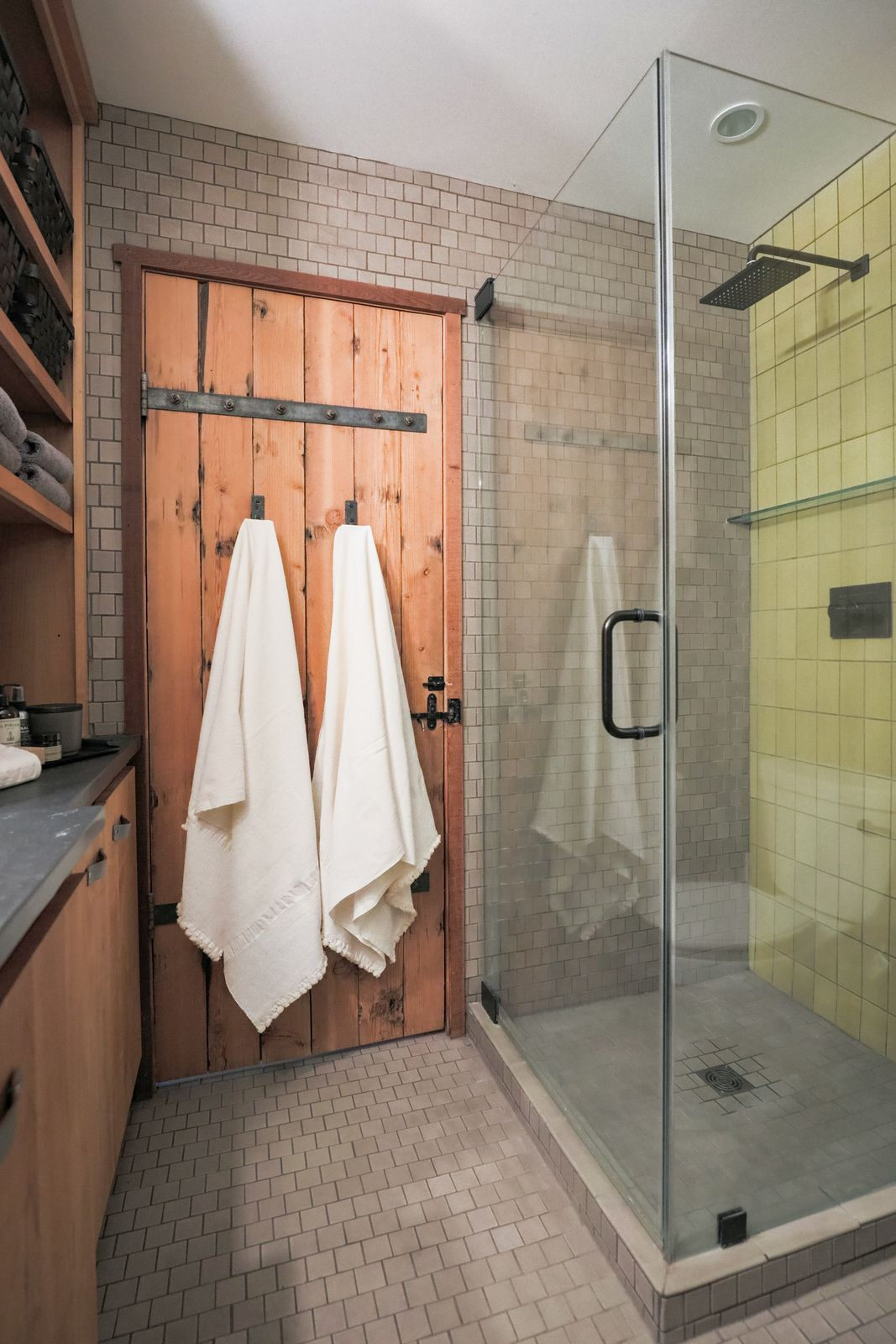 Glass shower door and shower covered in lime-green tile.