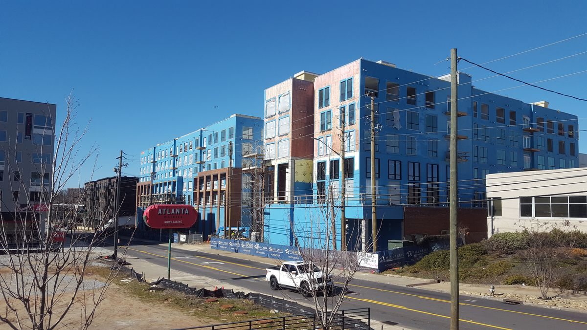 """A shot of Modera Reynoldstown from across the street, where a red sign says """"Atlanta Dairies."""""""