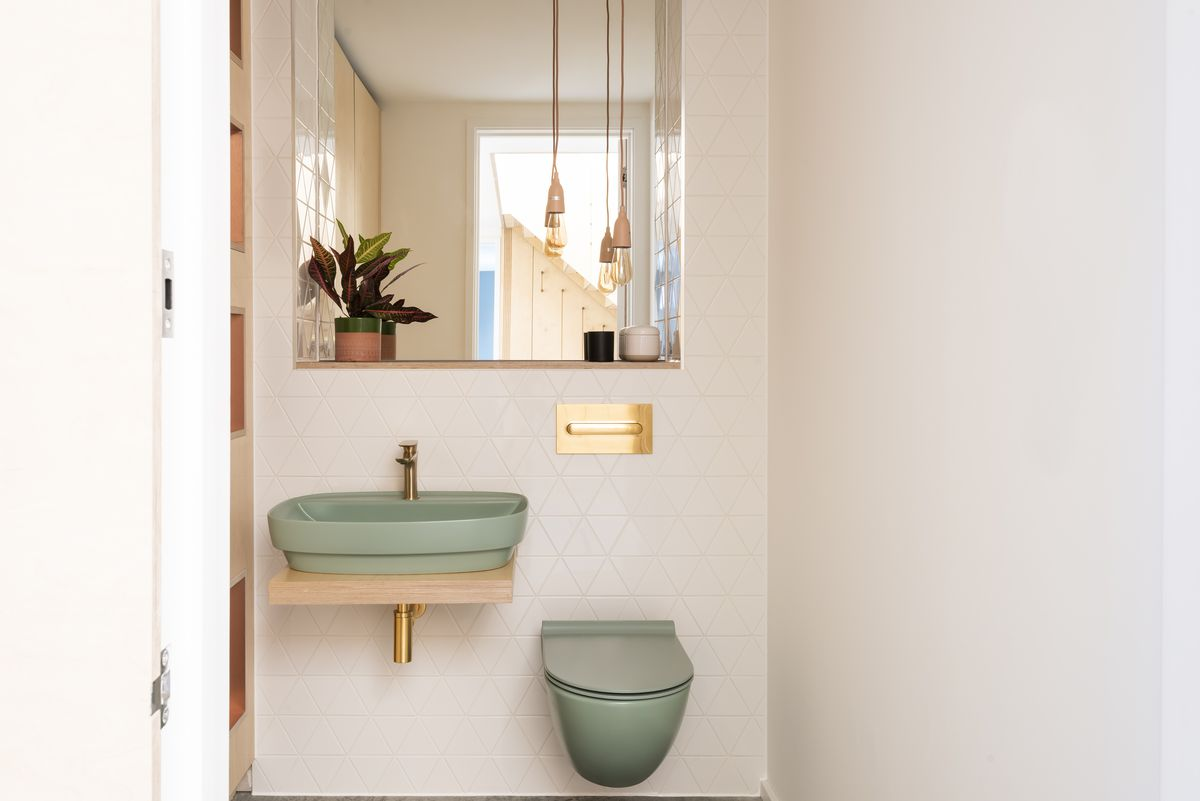 Bathroom with pastel green sink and toilet.