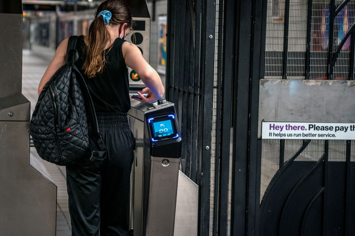 A commuter taps her phone on an OMNY pad at TimesSq-42 Street, Oct. 24, 2020.
