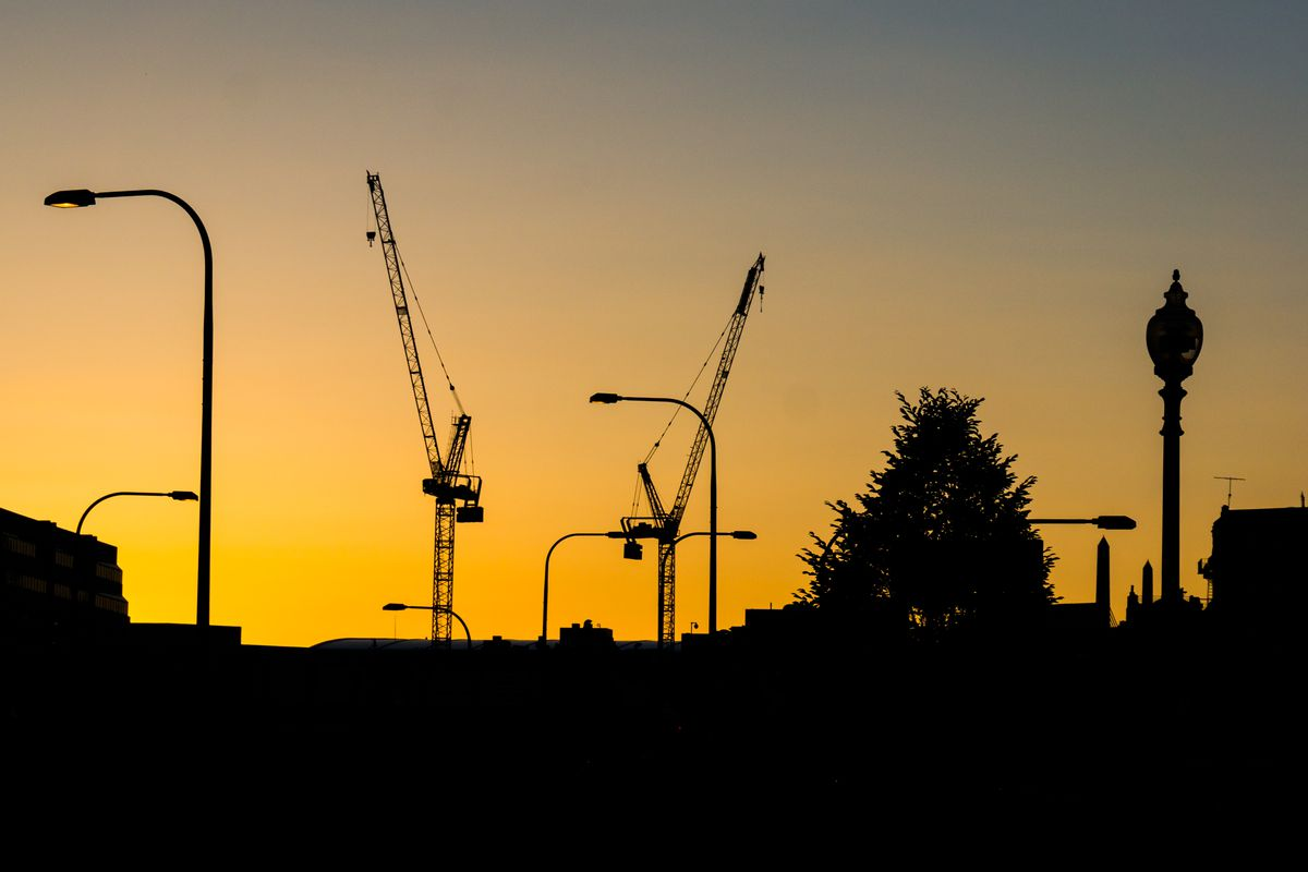Two construction cranes hovering over Boston.