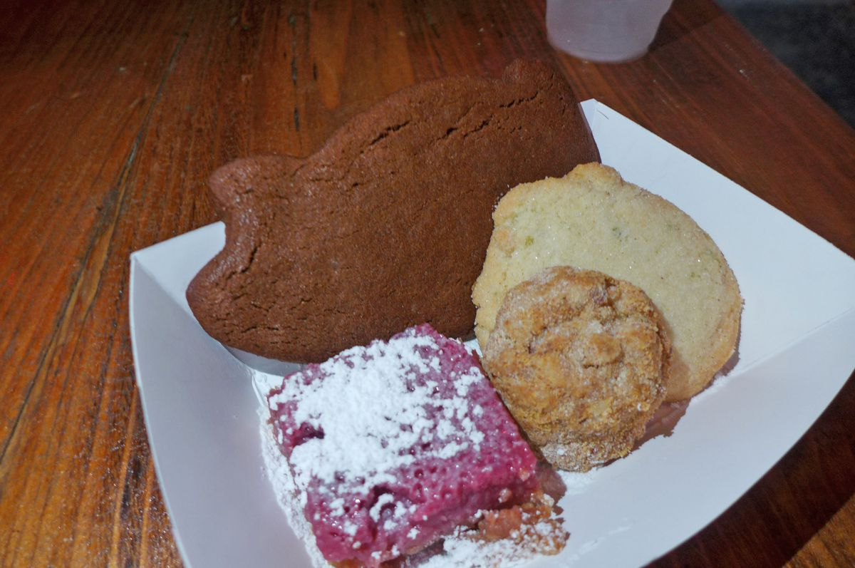 Four cookies including a giant brown one shaped like a pig.