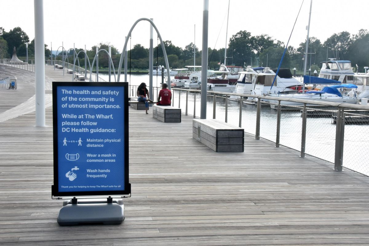 A sign at the Wharf development reminds people to maintain physical distance and wear a mask.