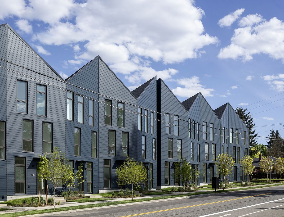 Facade of of blue townhouse development shows angular roofline and mismatched windows.