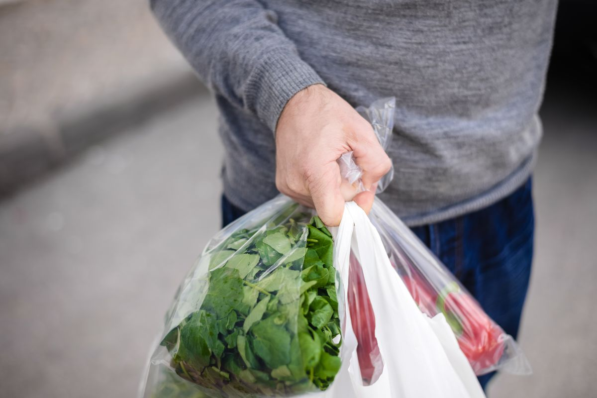 Man's hand carrying plastic bags with vegetables in them